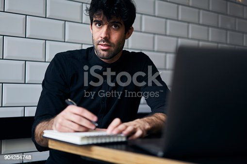 904263506 istock photo Bearded smart student studying and preparing for upcoming exam sitting in coffee shop interior with digital computer.Young hipster guy writing checklist with plans in notebook while free time 904254748