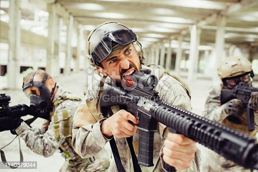 istock Bearded soldier is screaming and yelling. He has long rifle in his hands. Guy is standing in front of his combats. They are covering him from different sides. 1140379044