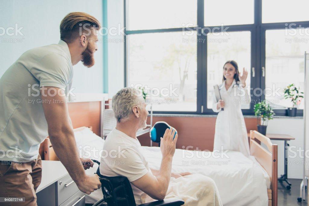 Barbu fils prend son vieux papa tête gris maison sur une chaise roulante de l'hôpital. Patient est wawing à la jeune infirmière - Photo