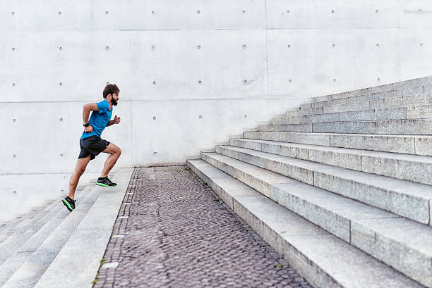 bearded sportsman running up outdoor stairway stock photo