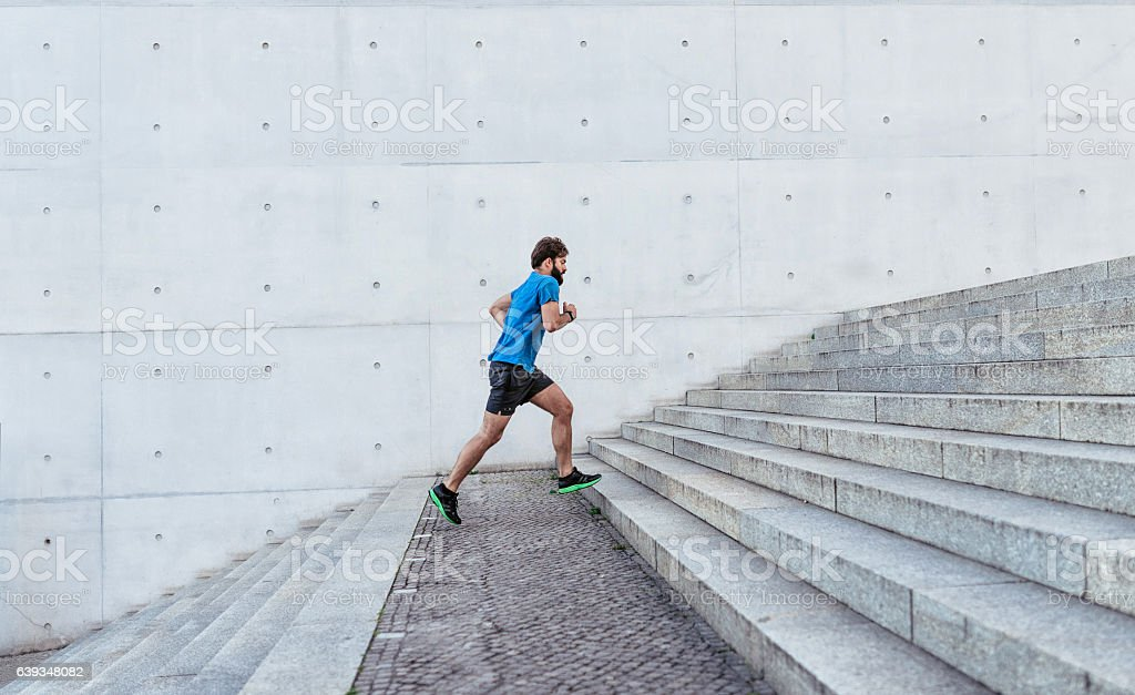 bearded sportsman running up stone stairway outdoors – Foto