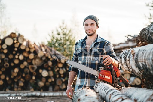 istock Bearded strong lumberjack wearing plaid shirt hold in hand chainsaw for work on sawmill 1042936418