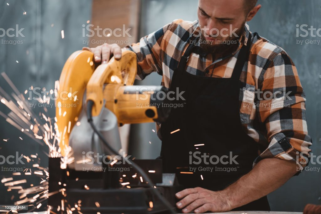 Bearded strong mechanic using electrical angular grinding machine at factory, sparks fly apart. Work in process on metalworking plant. Horizontal stock photo