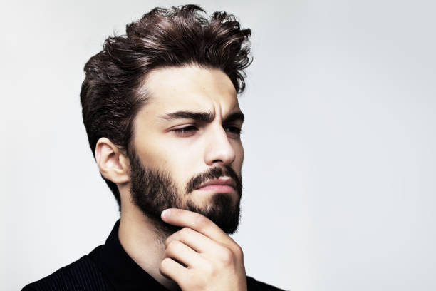 bearded stylish man posing outdoors - hairstyle stock photos and pictures