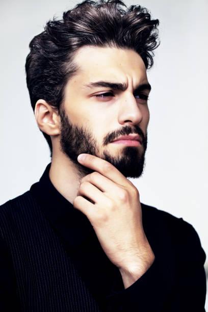 bärtige stilvollen mann posiert im freien - männerfrisuren stock-fotos und bilder