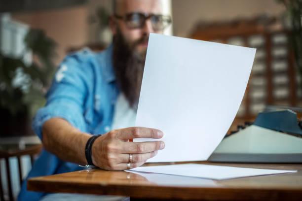 barbu élégant écrivain lisant son roman - étage photos et images de collection