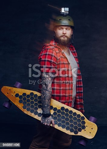 istock Bearded tattooed man holds Longboard. 946881496