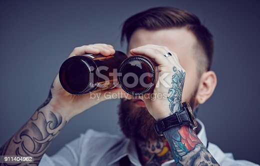 istock Bearded tattooed man looking through beer bootles. 911404962