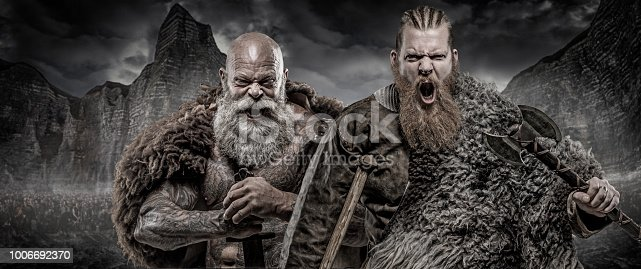 istock Bearded Tattooed Viking warrior king and prince in front of warrior hoard and background 1006692370