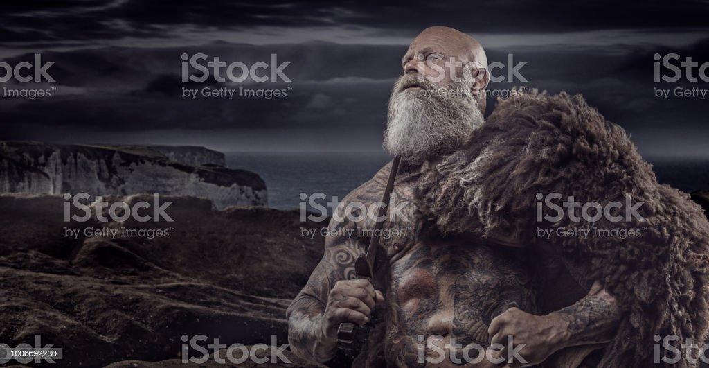 Rei-guerreiro Viking tatuado barbudo na frente do tesouro de guerreiro e fundo - foto de acervo