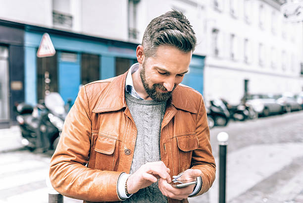 bearded tourist looking at mobile in streets of paris stock photo