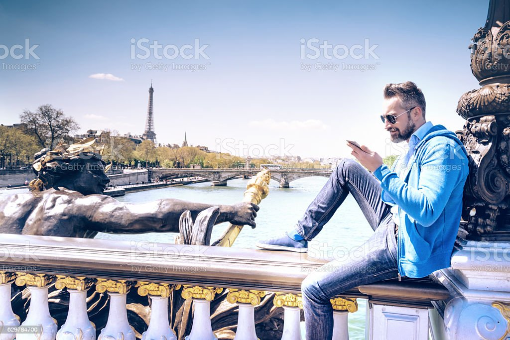 bearded tourist with mobile sitting on Pont Alexandre in paris stock photo