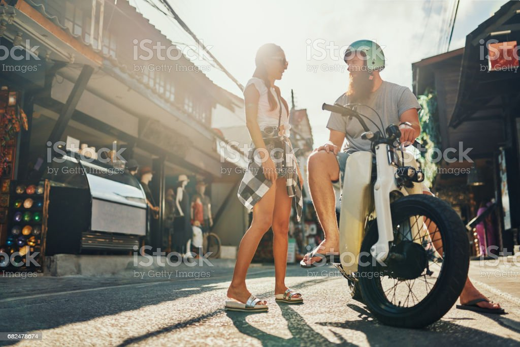 bearded western tourist on vintage motorbike flirting with woman foto stock royalty-free
