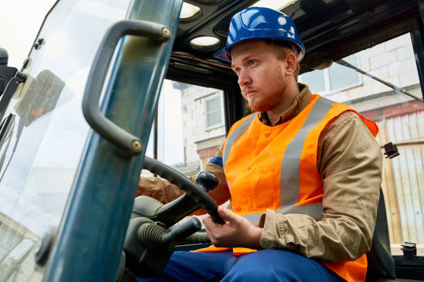 bearded worker driving lift truck - crane construction machinery stock pictures, royalty-free photos & images