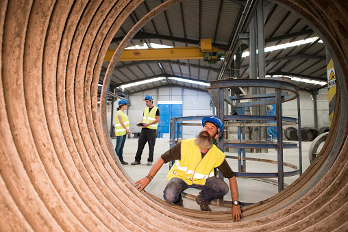 Bearded worker inspects the inside of a tubular structure in a cement and infrastructure construction company
