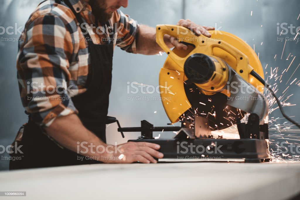 Bearded worker mechanic using electrical angular grinding machine in metalworking plant. Work in action. Sparks fly apart. Horizontal stock photo