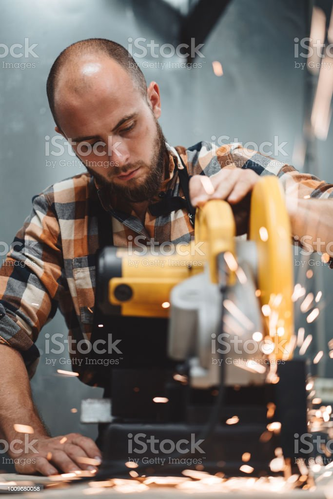 Bearded worker mechanic using electrical angular grinding machine in metalworking. Work in action. Sparks fly apart. Vertical stock photo