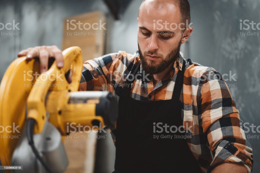 Bearded worker using electrical angular grinding machine in workshop. Servicing of machines. Workflow at the metalworking factory stock photo
