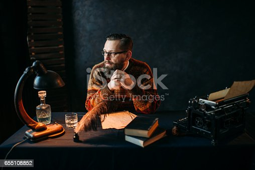 655113470 istock photo Bearded writer in glasses sitting at the table 655108852