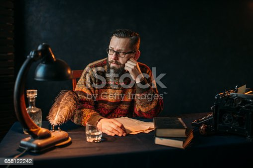 655113470 istock photo Bearded writer in glasses sitting at the table 658122242