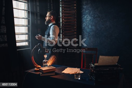 655113470 istock photo Bearded writer in glasses smoking a cigarette 655113304
