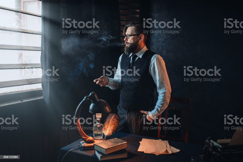 Bearded writer in glasses smoking a cigarette royalty-free stock photo
