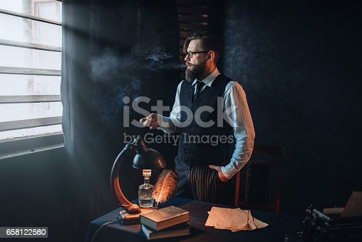 655113470 istock photo Bearded writer in glasses smoking a cigarette 658122580