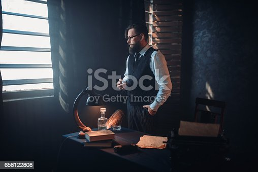 655113470 istock photo Bearded writer in glasses smoking a cigarette 658122808