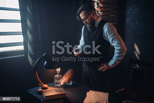 655113470 istock photo Bearded writer in glasses smoking a cigarette 663371714