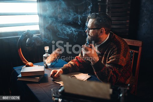 655113470istockphoto Bearded writer in glasses smoking a pipe 655113276