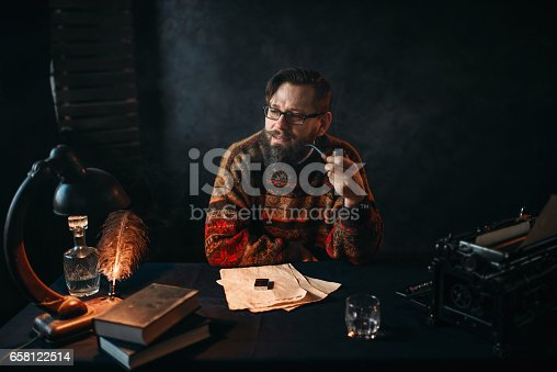655113470 istock photo Bearded writer in glasses smoking a pipe 658122514