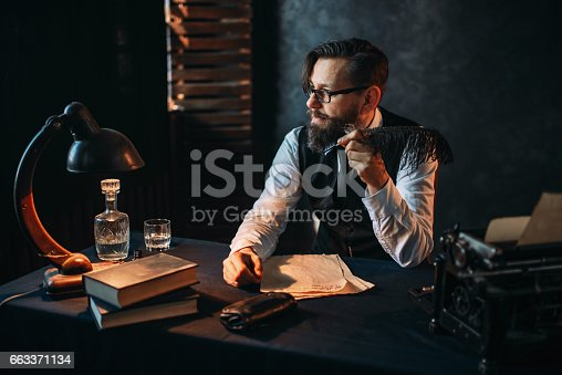 655113470 istock photo Bearded writer in glasses smoking a pipe 663371134