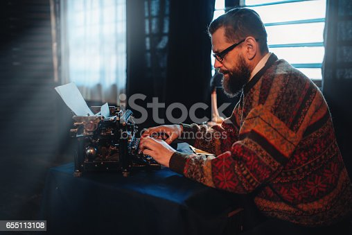 655113470 istock photo Bearded writer in glasses typing on a typewriter 655113108