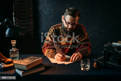 655113470 istock photo Bearded writer in glasses writes with a feather 655113142