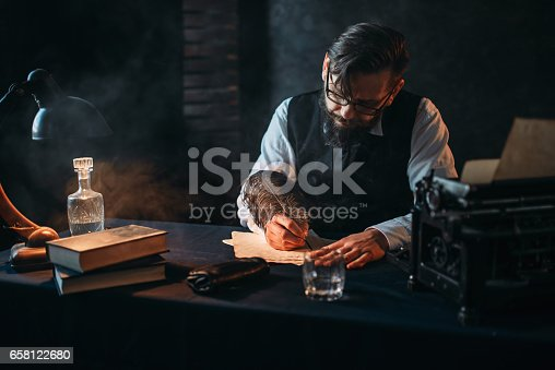 655113470 istock photo Bearded writer in glasses writes with a feather 658122680