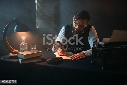 655113470 istock photo Bearded writer in glasses writes with a feather 658122774