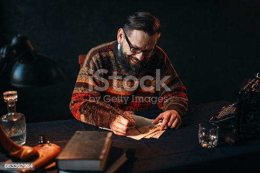 655113470 istock photo Bearded writer in glasses writes with a feather 663362964