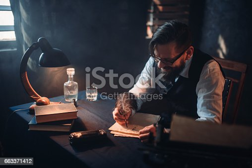 655113470 istock photo Bearded writer in glasses writes with a feather 663371412