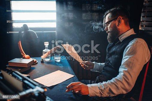 655113470 istock photo Bearded writer smokes and reads handwritten text 655113502