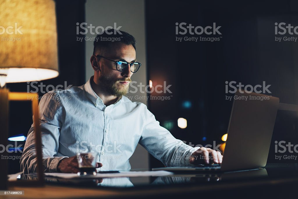 Bearded young businessman wearing white shirt working on modern loft stock photo