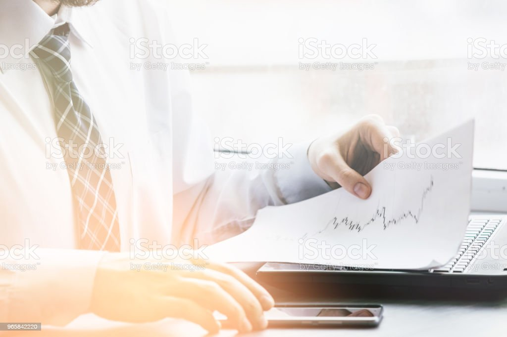 Bearded young businessman working at modern office.Man wearing white shirt and making notes on the documents.Panoramic windows background. Horizontal, film effect.Blurred Light toning - Royalty-free Adult Stock Photo