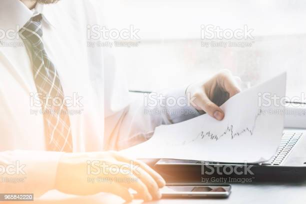 Bearded Young Businessman Working At Modern Officeman Wearing White Shirt And Making Notes On The Documentspanoramic Windows Background Horizontal Film Effectblurred Light Toning Stock Photo - Download Image Now