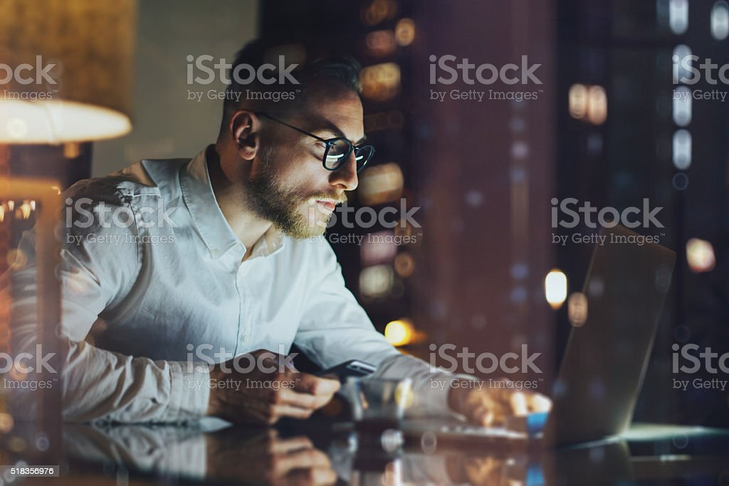 Bearded young businessman working on modern loft office at night - Royalty-free Adult Stock Photo