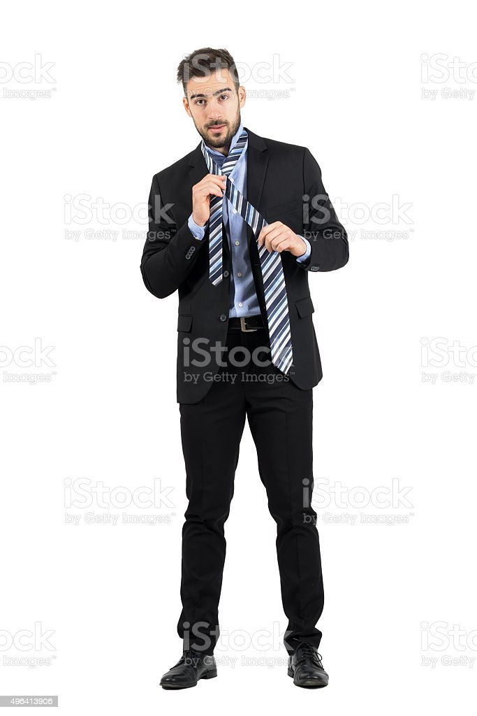 Bearded young corporate man tying necktie looking at camera. stock photo