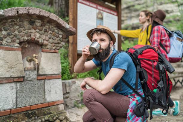 bärtiger junger wanderer ruhen in den frühling-wasserhahn - leitungswasser trinken stock-fotos und bilder