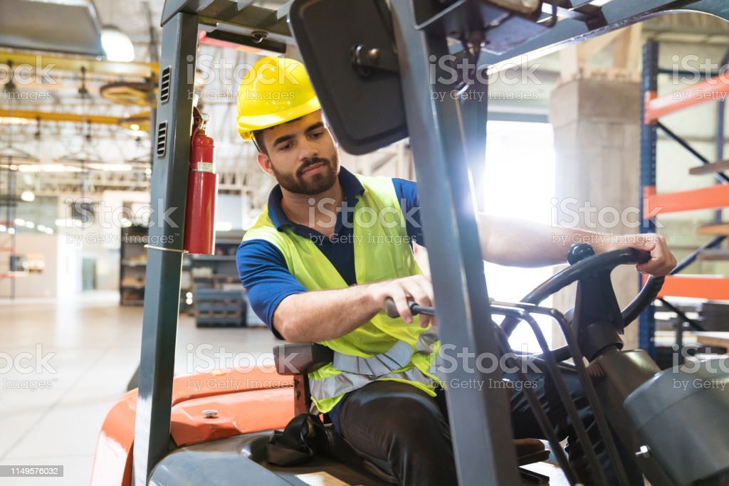 Bearded young man driving forklift in factory Bearded young man driving forklift in factory. Manual worker is working in warehouse. He is occupied in manufacturing. 20-24 Years Stock Photo