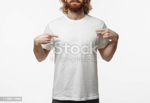 1018069806 istock photo Bearded young man in pointing to his blank white t-shirt with index fingers, showing empty space for your advertising text or logo, standing isolated on gray background 1128512888