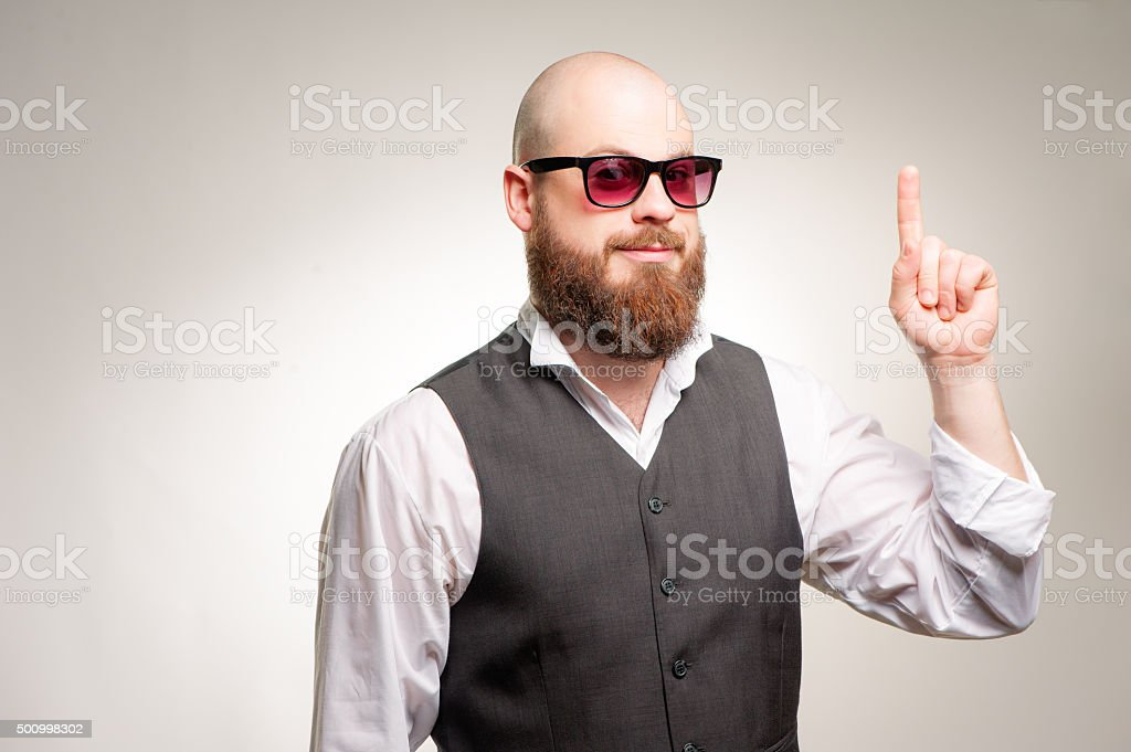 bearded young man in sunglasses pointing up stock photo