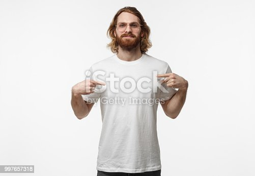 1018069806 istock photo Bearded young man in trendy glasses pointing to his blank white tshirt with index fingers, showing empty space for your advertising text or logo, standing isolated on grey background 997657318