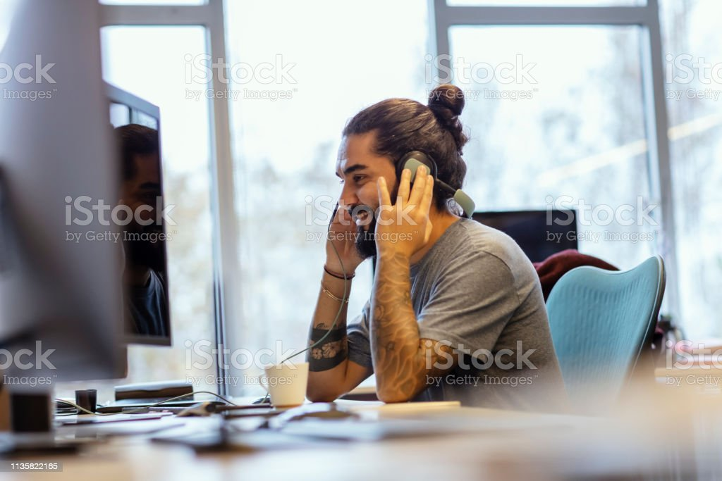 Bearded Young Man Listening Music and Relaxing at Office